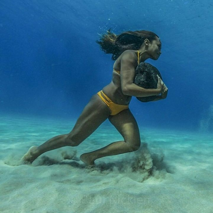 2. surfer walking on the seabed with a 20-pound stone impact resistance training waves in the world, people, photos
