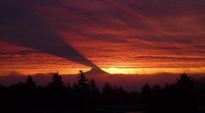 Гора, отбрасывающая тень на облака.