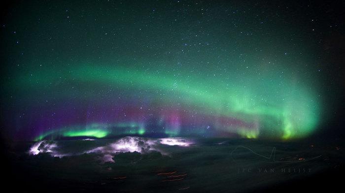 Прекрасное северное сияние в небе над Канадой, которое подсвечивается снизу несколькими грозами с молниями.