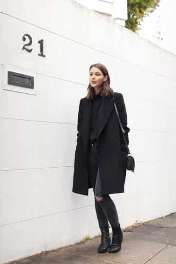 Девушка в серых, рваных джинсах и черном пальто