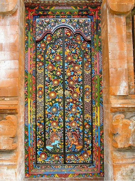 Яркая дверь, украшенная разноцветной мозаикой.