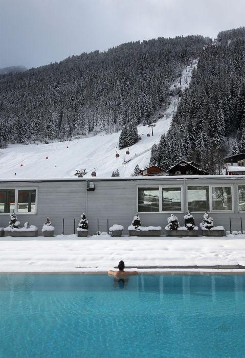 Бассейн с термальной водой и снежные горы с подъемниками смотрятся сказочно и необычно.