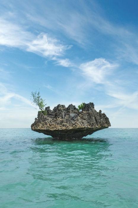 Небольшой одинокий остров с зелеными насаждениями в водах океана.