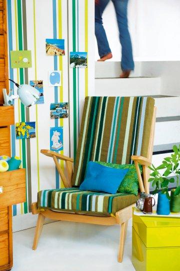 Скандинавской кресло украшены цветными полосами цвета хаки кожи и полосы на стене