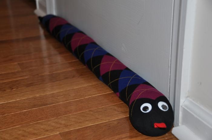 Из старых длинных носков получится отличный «антисквозняк». /Фото: engagingtoddleractivities.files.wordpress.com