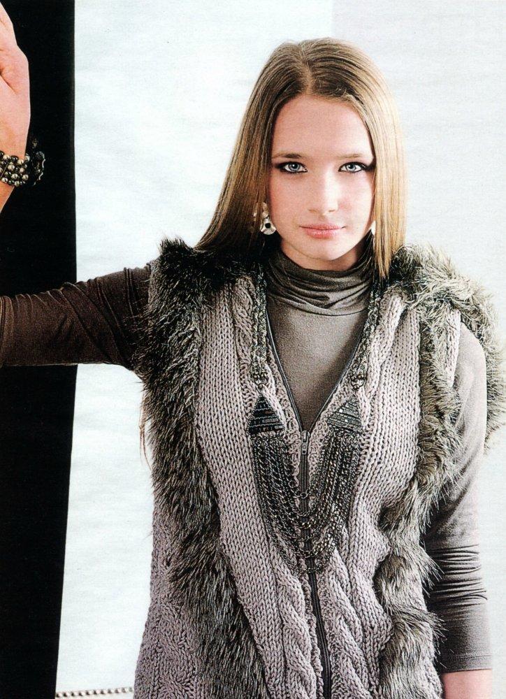 Стильный вязаный спицами жилет с мехом на девушке