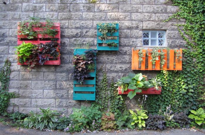 Кашпо для цветов из частей европоддонов, раскрашенных в яркие цвета.