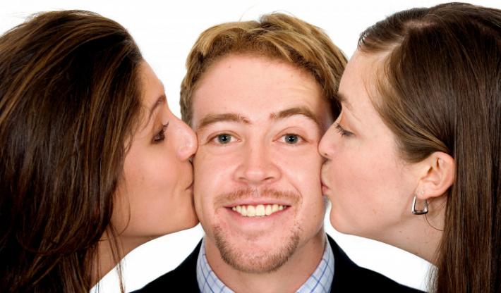 две женщины целуют мужчину