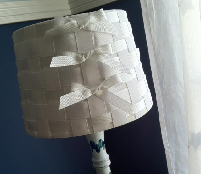 Обычные атласные ленты, переплетённые в шахматном порядке, и сделанные из них жантильные бантики могут придать настольной лампе удивительно элегантный вид.