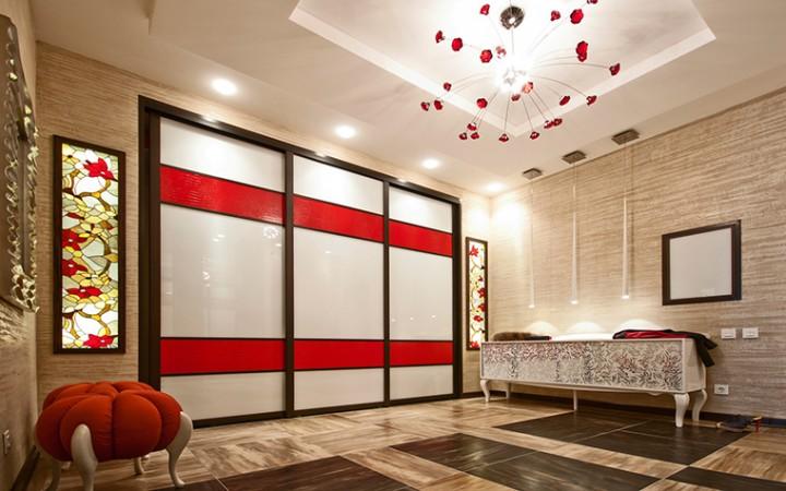 <p>На фото - оригинальный дизайн большой прихожей. Автор проекта: Виктория Нерсесянц.</p> <p>Если  большая прихожая располагает лишним пространством, то можно устроить там небольшую гостиную. Оформить ее можно эффектно и выразительно.  Например,  соединить  ярко красный пуф,  разноцветные витражи и люстру из «рубинового» стекла.</p>