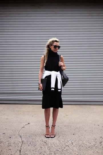 Девушка в черном платье с белым свитером, обвязанном вокруг талии