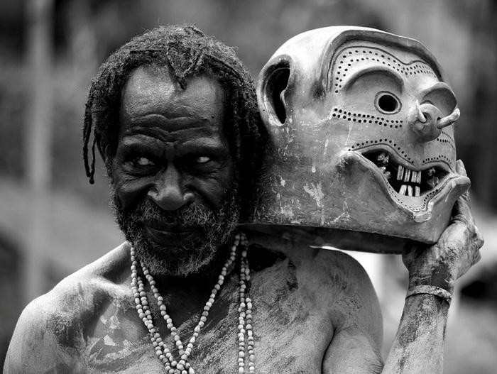 Мужчина, обмазанный глиной в ритуальной маской в руке