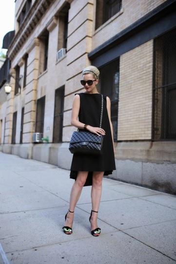 Девушка в черном платье и босоножках с глазами
