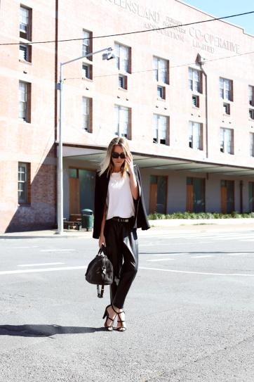 Девушка в кожаных штанах, белом топе и жакете
