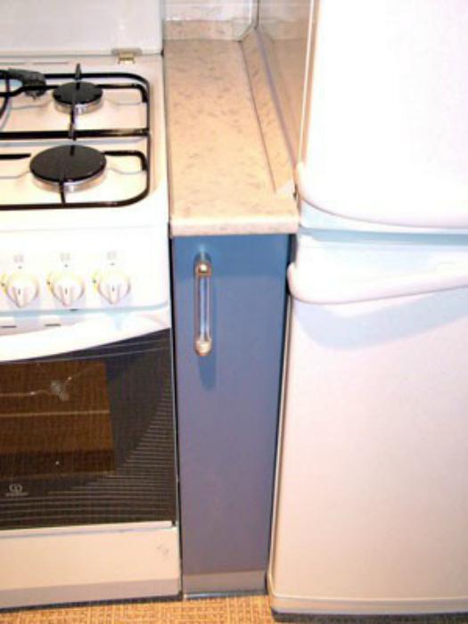 Узкий шкафчик между плитой и холодильником.