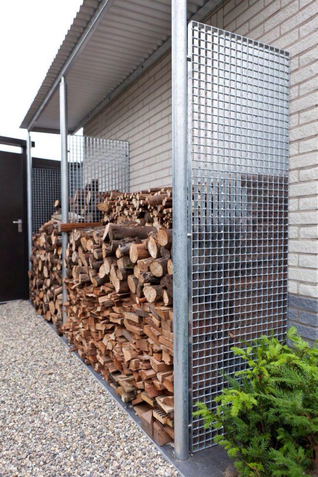 Небольшой навес для хранения дров, размещенный на свежем воздухе прямо у фасада дома