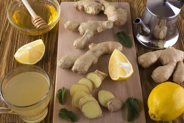 кусочки свежего имбиря, лимон и листья мяты на разделочной доске, имбирный чай в стакане и заварник