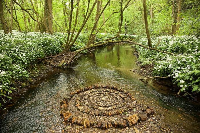Спираль, тщательно выложенная из мокрых камней посредине лесной реки.