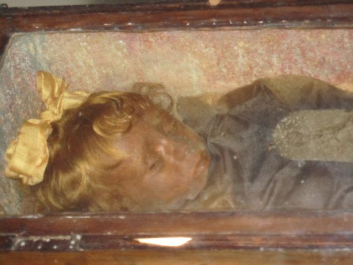Розалия ломбардо - девочка, которая словно заснула в гробу. <br>  <p> Розалия Ломбардо - девочка, которая словно заснула в гробу.</noindex></center><br> <br> Мумиями в современном мире уже никого не удивишь, но есть среди всех существующих одна, которая приковывает к себе немало внимания. Зовут ее Розалия Ломбардо. Это мумия двухлетней девочки, которая ушла из жизни, прожив всего пару лет. Ее отец, убитый горем, принял решение бальзамировать тело девочки. Исполнитель заменил кровь в теле ребенка на формальдегид, обработал всю поверхность тела специальным составом и предупредил развитие грибка. Работа мастера дала потрясающие результаты — с момента смерти Розалии прошел уже век, а выглядит она очень даже живой, но просто заснувшей. <br>  <h2>2.Клетки для мертвецов</h2><p><center><noindex>[img src=