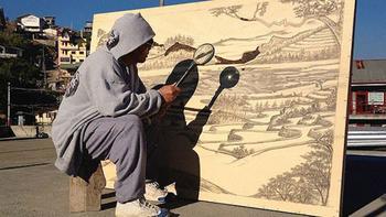 Художник рисует при помощи лупы и солнечного света