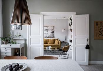 Двухуровневая квартира с жёлтым диваном и тумбочками из ящиков в Гётеборге
