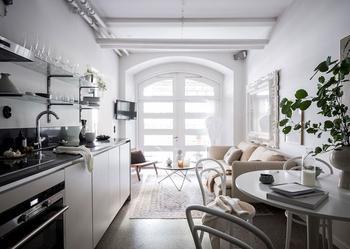 Маленькая белая квартира с одним большим окном и классическим зеркалом
