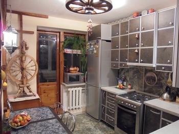 Кухня: прялка, глиняные сувениры, люстра из колеса от телеги