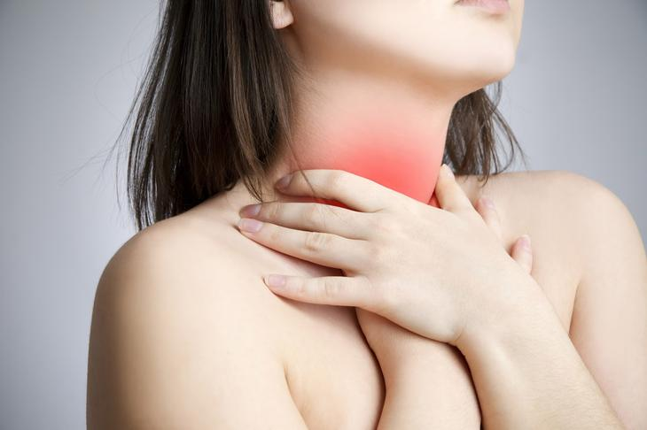 Sore throat of a women. Touching the neck.
