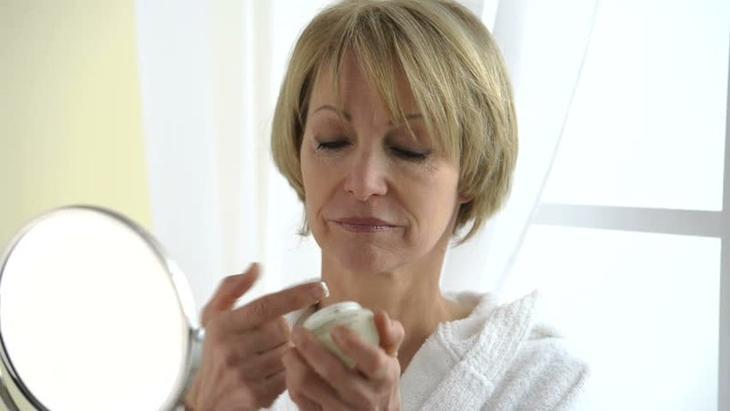 Женщина после 50 увлажняет лицо