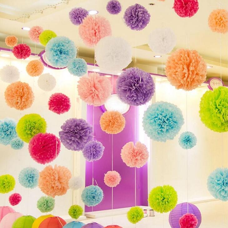 Разноцветные помпоны из крепированной бумаги висят в комнате