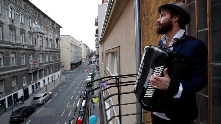 Один из жителей Будапешта (Венгрия) играет для других жителей города, вынужденных быть дома, 22 марта 2020 года