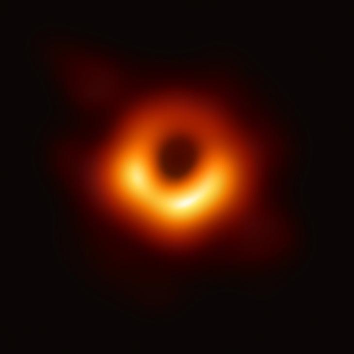 Силуэт черной дыры M87 — черная окружность в центре. Менее яркая часть кольца вокруг нее расположена с дальней от земного наблюдателя стороны черной дыры / ©Wikimedia Commons