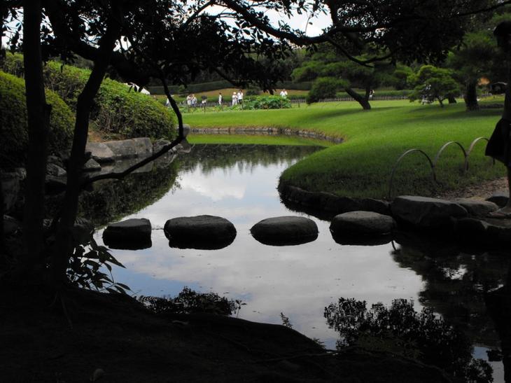 Японский парк Кераку-эн летом. Пруд с камнями. Фото