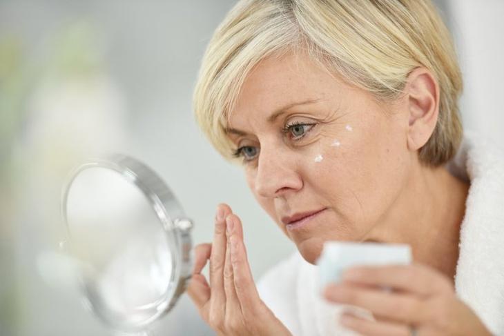 Женщина питает лицо кремом